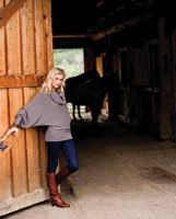 a woman models a sweater next to a barn door
