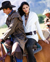 a woman models a white blouse while on the back of a horse