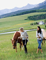 two women in fall sweaters holding horses