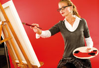 a woman in front of an easel