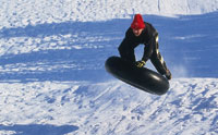sledding on an inner tube on a snowy slope