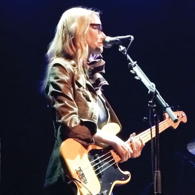 Aimee Mann performing with guitar in hand.