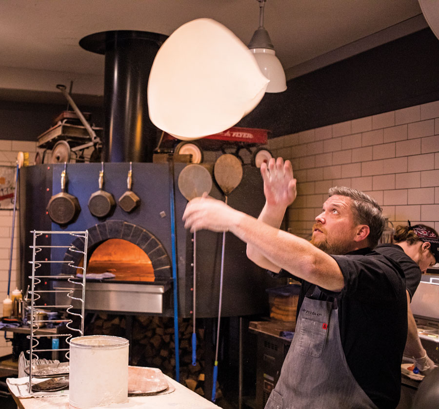 A chef flipping pizza dough at Red Wagon Pizza.