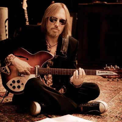 Tom Petty sitting on the floor playing guitar.