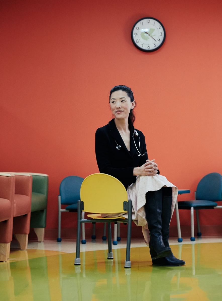 A portrait of Dr. Judy Eckerle sitting on a chair in a patient lobby.