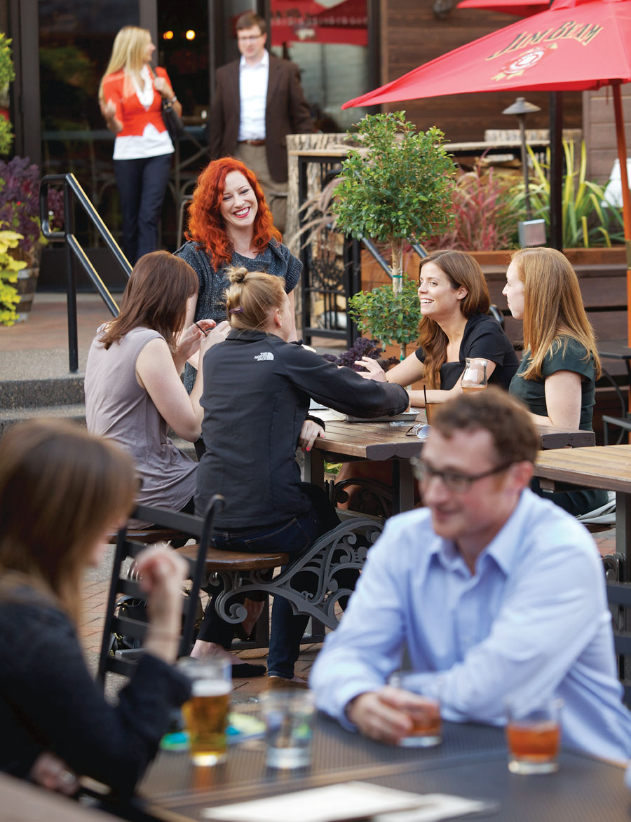 People dining and enjoying drinks on the patio at Buther & the Boar in downtown Minneapolis.