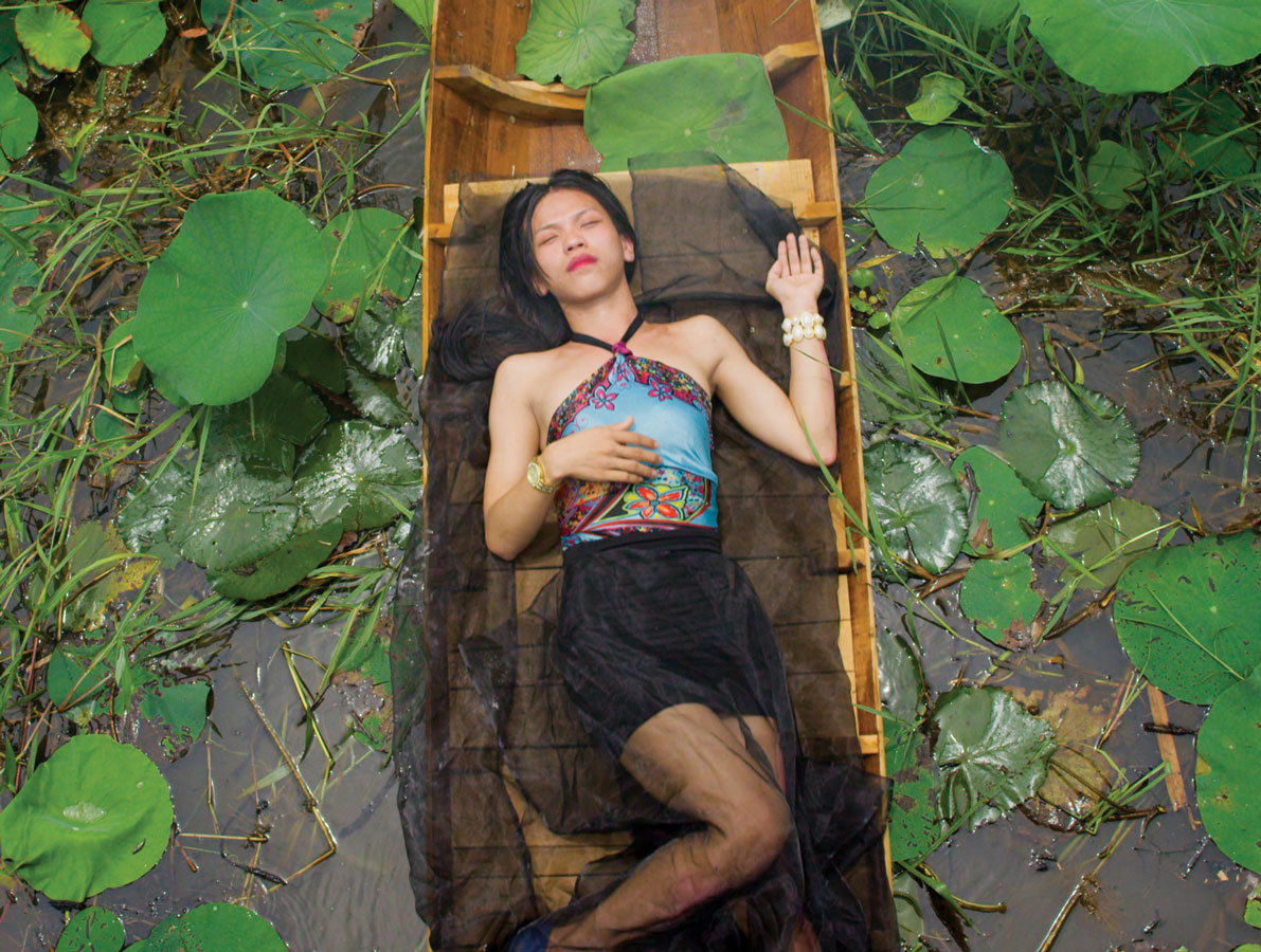 A girl laying in a boat in the middle of a swamp.