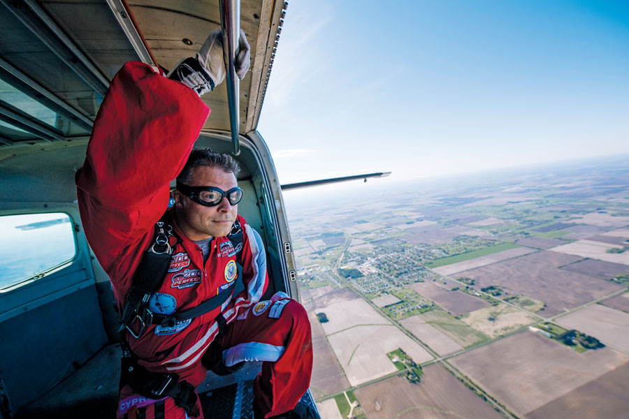 Kevin Burkhart getting ready to jump out of a plane high above farmland.