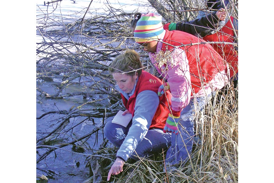 Children learning outdoors at a frozen lake in winter.