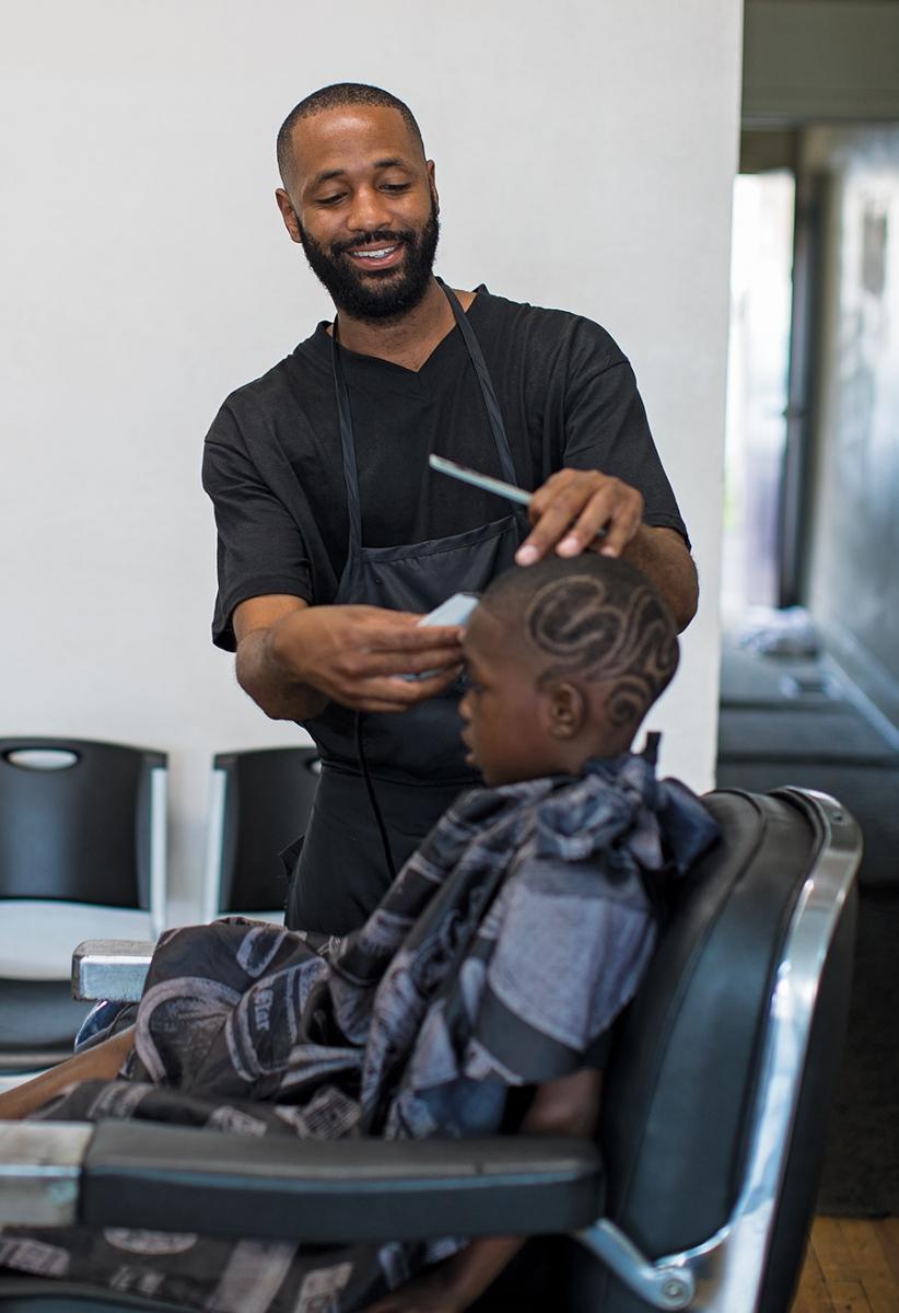 Milan Dennie of King Milan's Barbershop cutting a boy's hair.