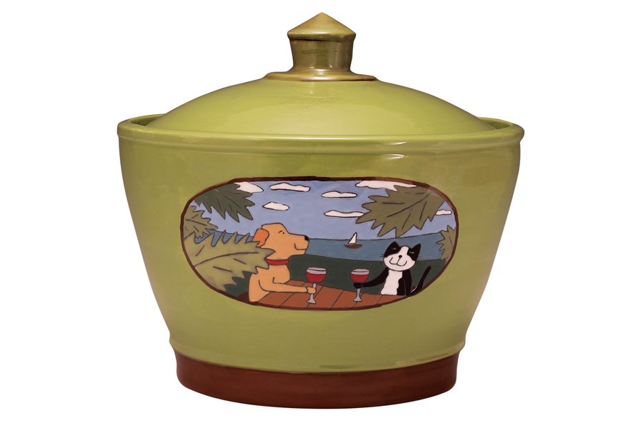 A green ceramic jar with a picture of a dog and a cat sitting at a table on the beach having a drink.