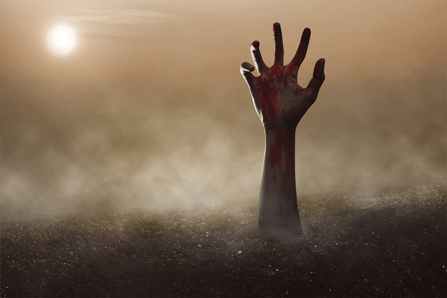 A zombie hand reaching toward the sky from the ground.