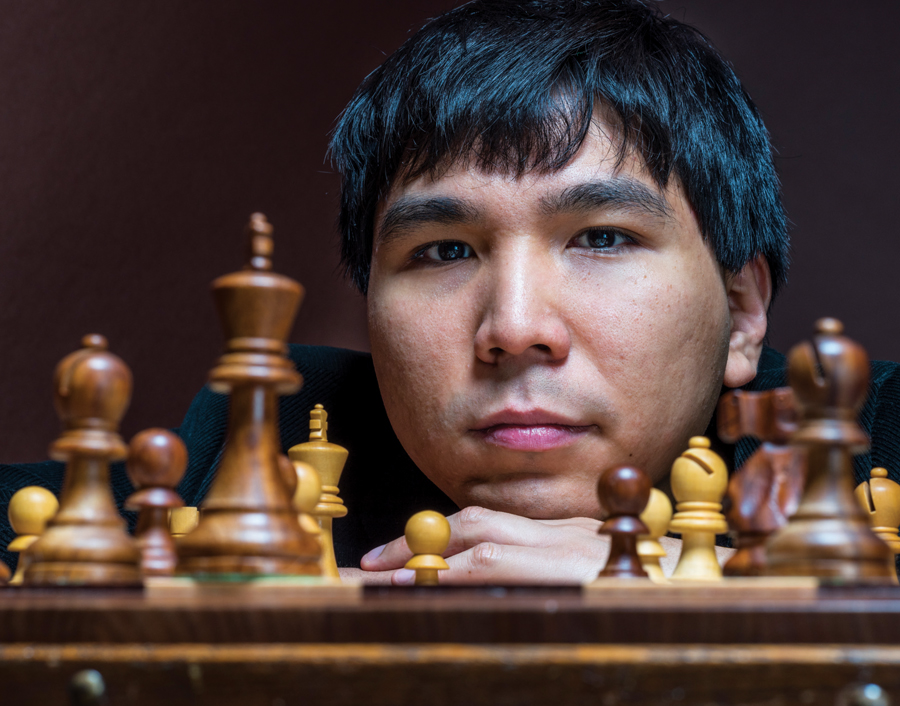 An close-up of Wesley So's head resting on his hand next to a chessboard.