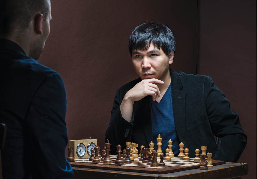 Wesley So resting his chin on his hand as he stares down his opponent during a game of chess.