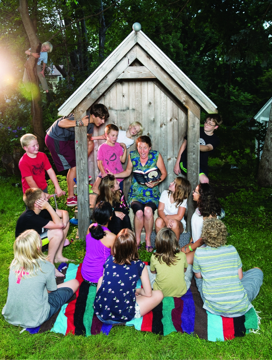 Author Kelly Barnhill reading to a bunch of children in a backyard.