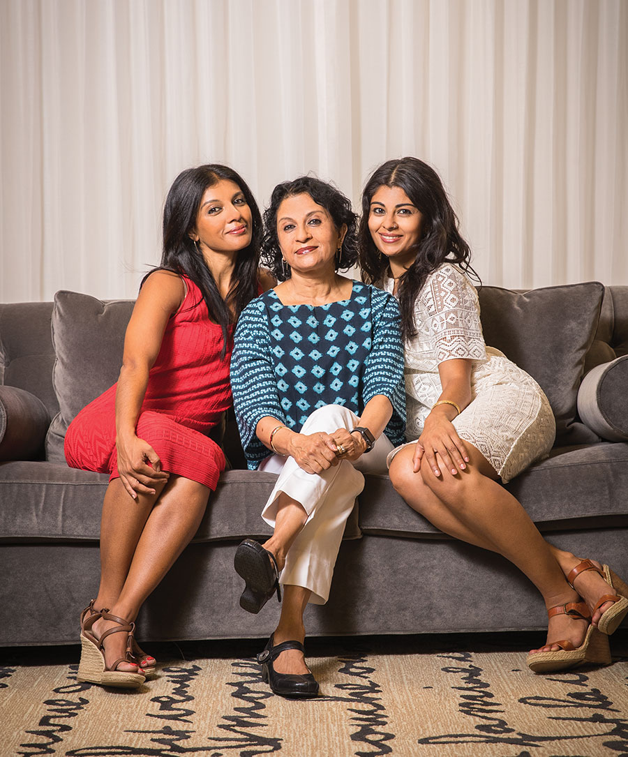 A portrait of Ranee Ramaswamy and her two daughters Aparna and Ashwini sitting on a couch.