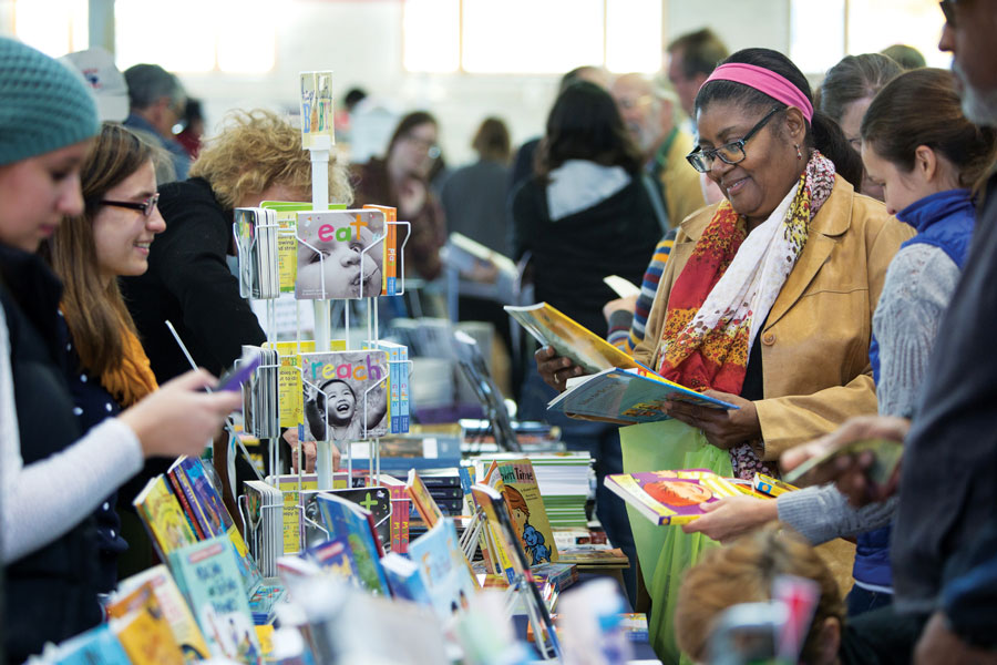 A group of people opening and reading books at the Twin Cities Book Festival.