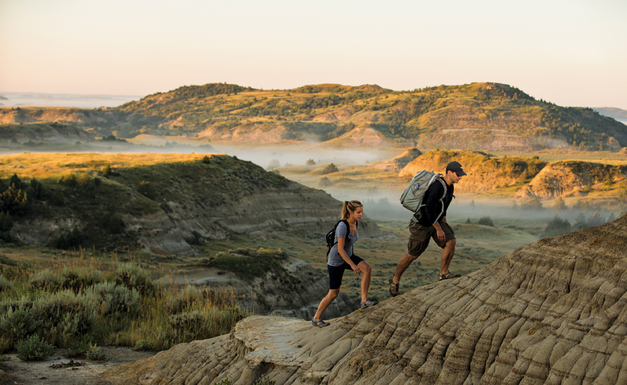 A couple hiking in the badlands at Theodore Roosevelt National Park in North Dakota.