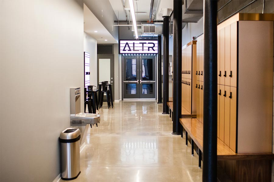 A hallway leading to the gym at ALTR in Minneapolis' North Loop consists of lockers on the right side, and a station for getting ready on the left.