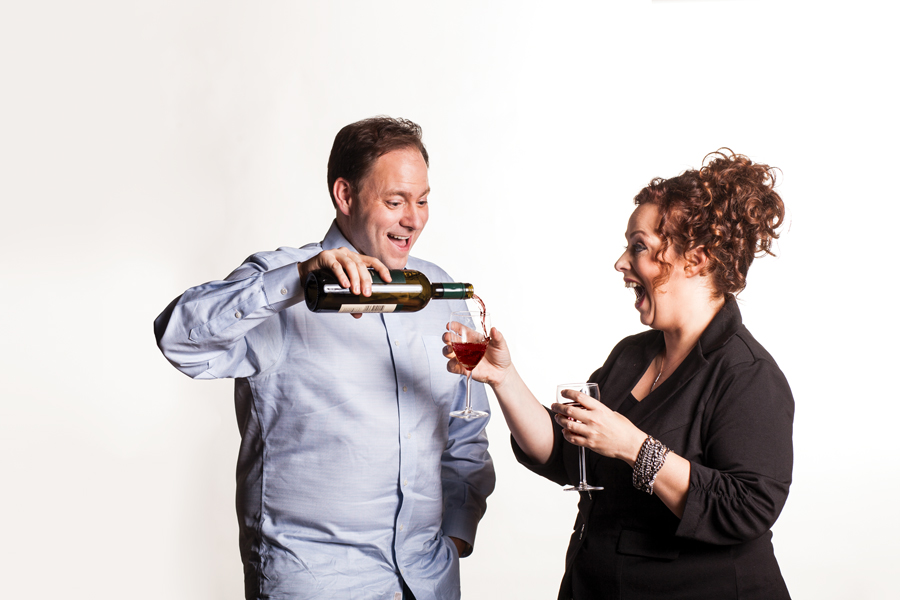 Jason DeRusha pouring wine into a glass held by Joy Summers.