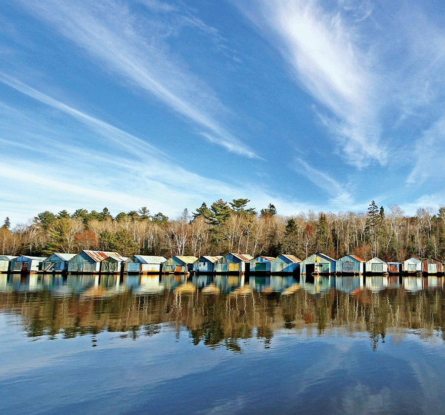 Corrugated-steel boathouses sitting on a calm lake with a forest in the background on a sunny day on Lake Vermillion in northern Minnesota.