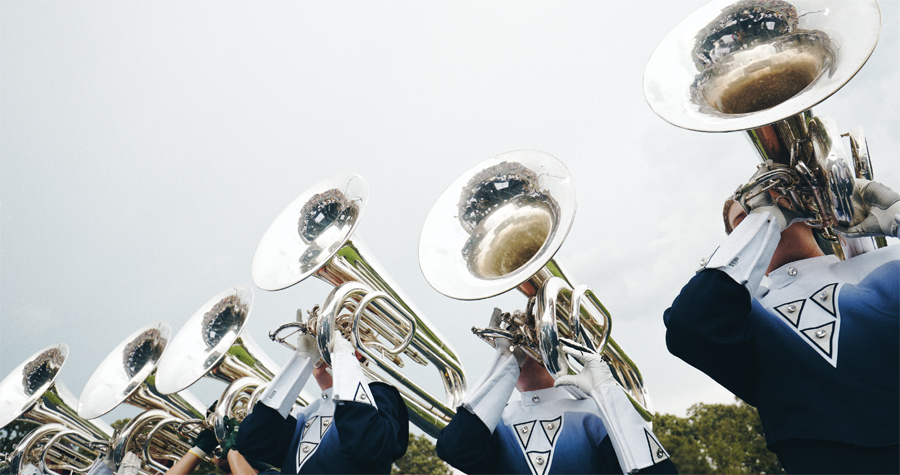 A group of marching band members holding and playing tubas above their heads.