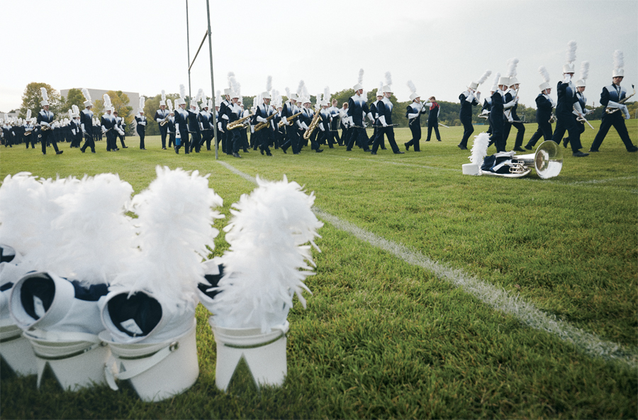 A collection of marching band hats with plumes in the foreground with the Rosemount marching band practicing in the background on a football field.