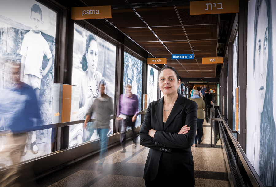 Nancy Ann Coyne standing in a St. Paul skyway with pictures of Minnesota immigrants on the individual panes.
