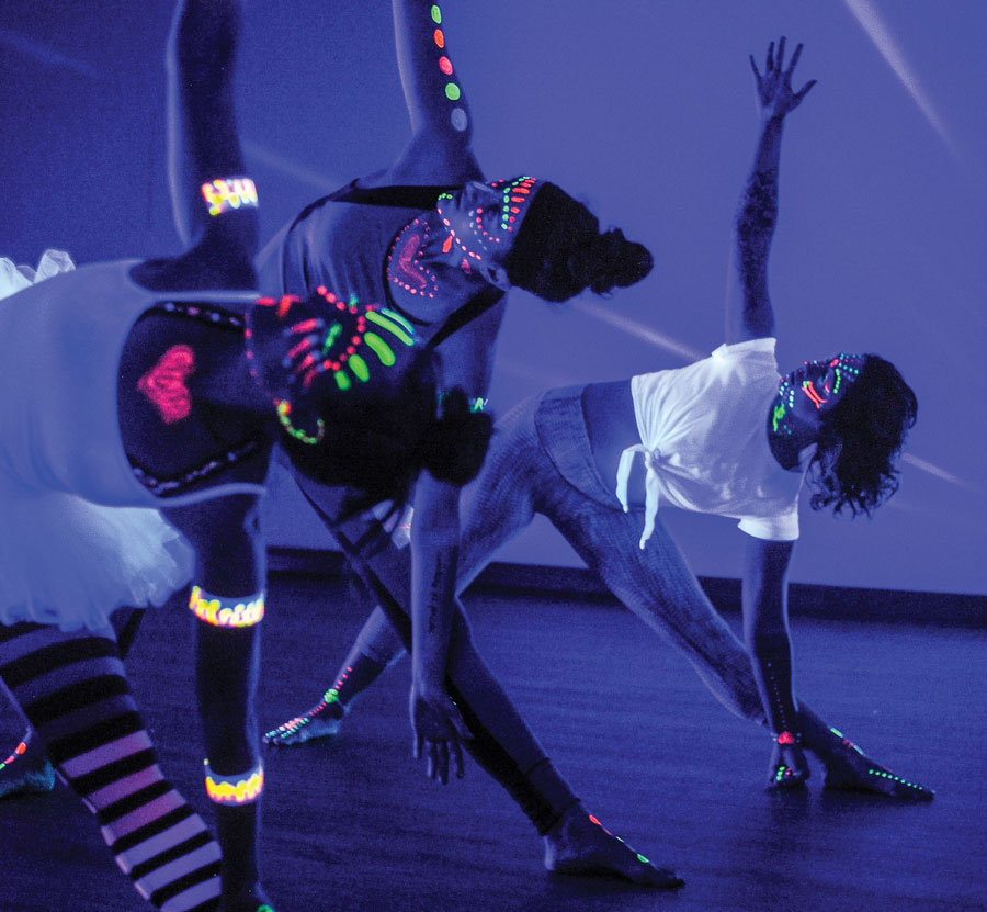 People with neon paint doing black-light yoga.