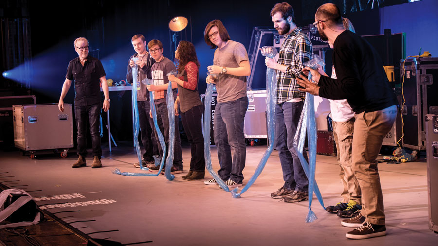 Seven people on stage holding long blue tubes of plastic.