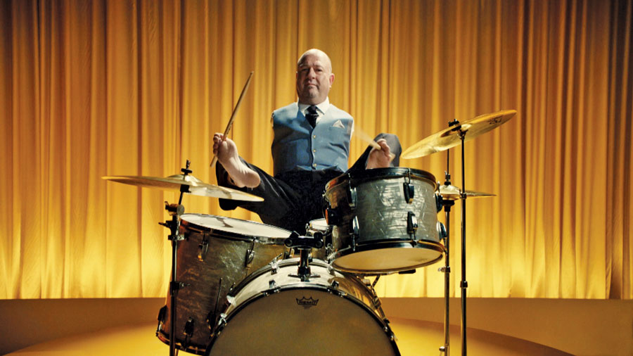 A man with no arms playing the drums with his feet.