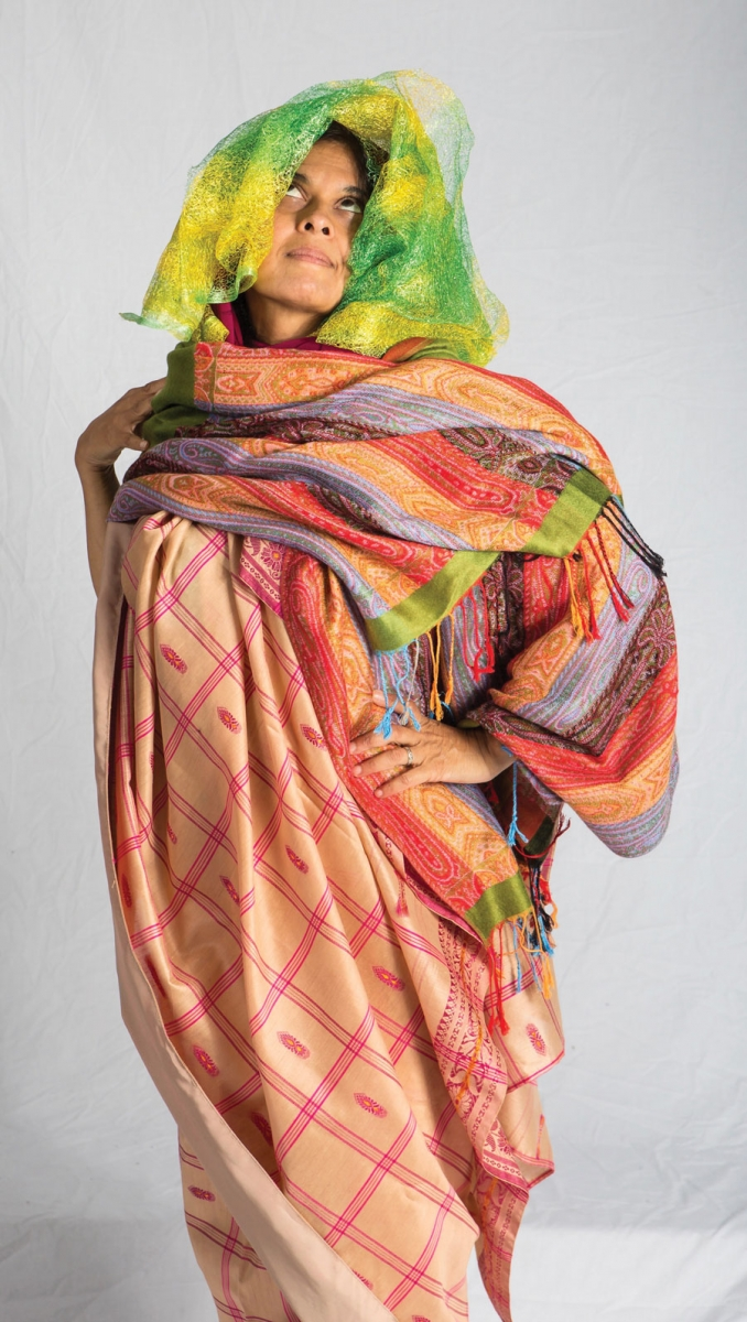 A lady posing with her hands on her hips and looking up while dressed in a colorful robe.