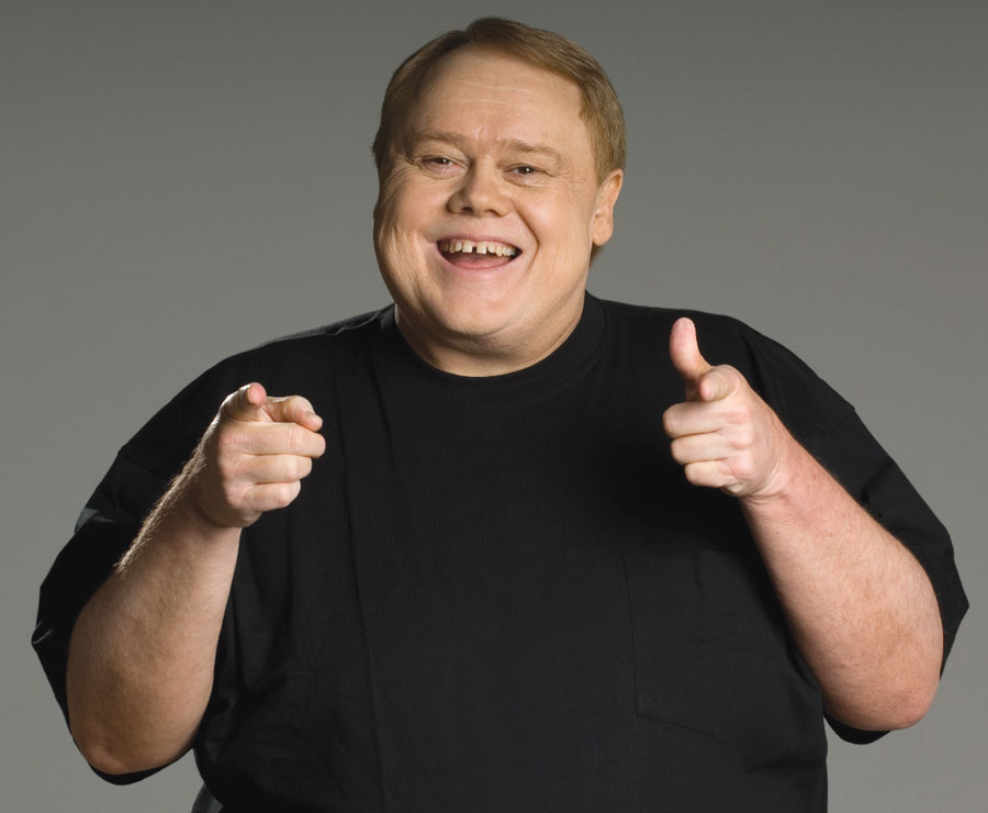 A portrait of comedian Louis Anderson smiling and finger gunning the camera.