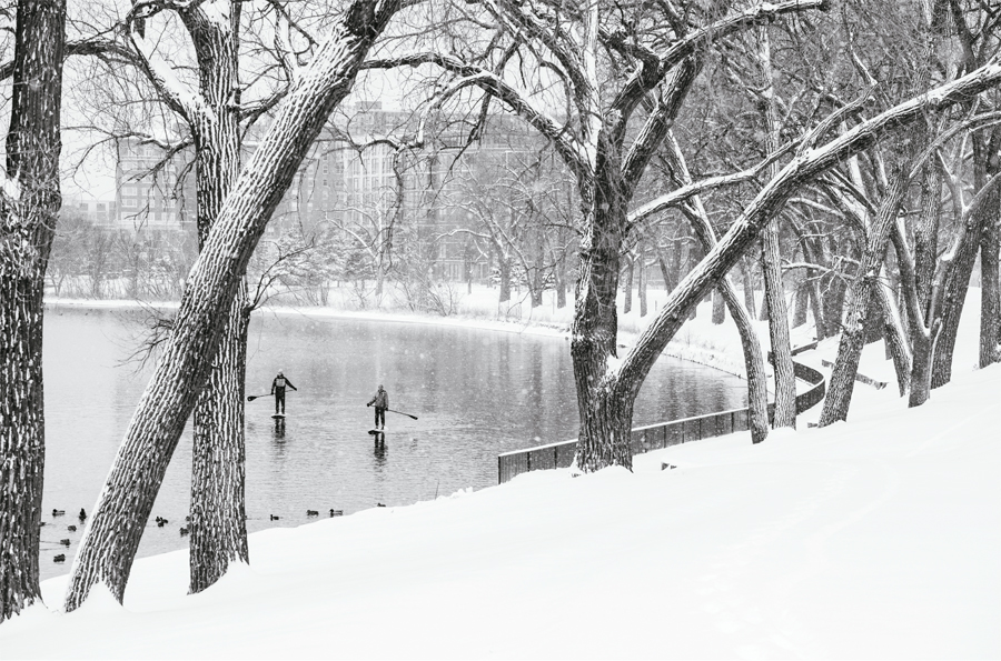 Two people stand-up paddleboarding on Lake Calhoun in Minneapolis in the middle of winter.