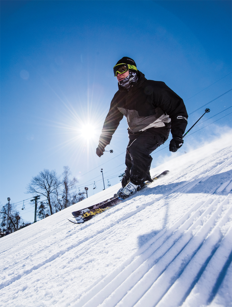 A skier skiing down a on a sunny day.
