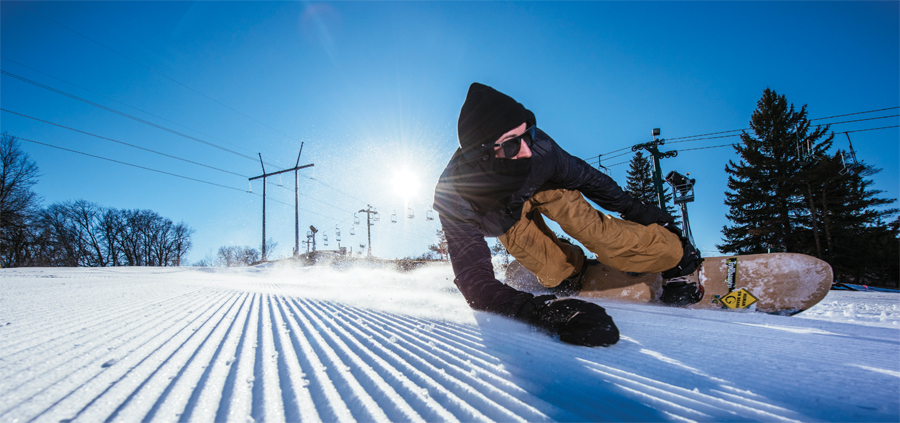 A snowboarder going down a hill and reaching down to touch the snow.