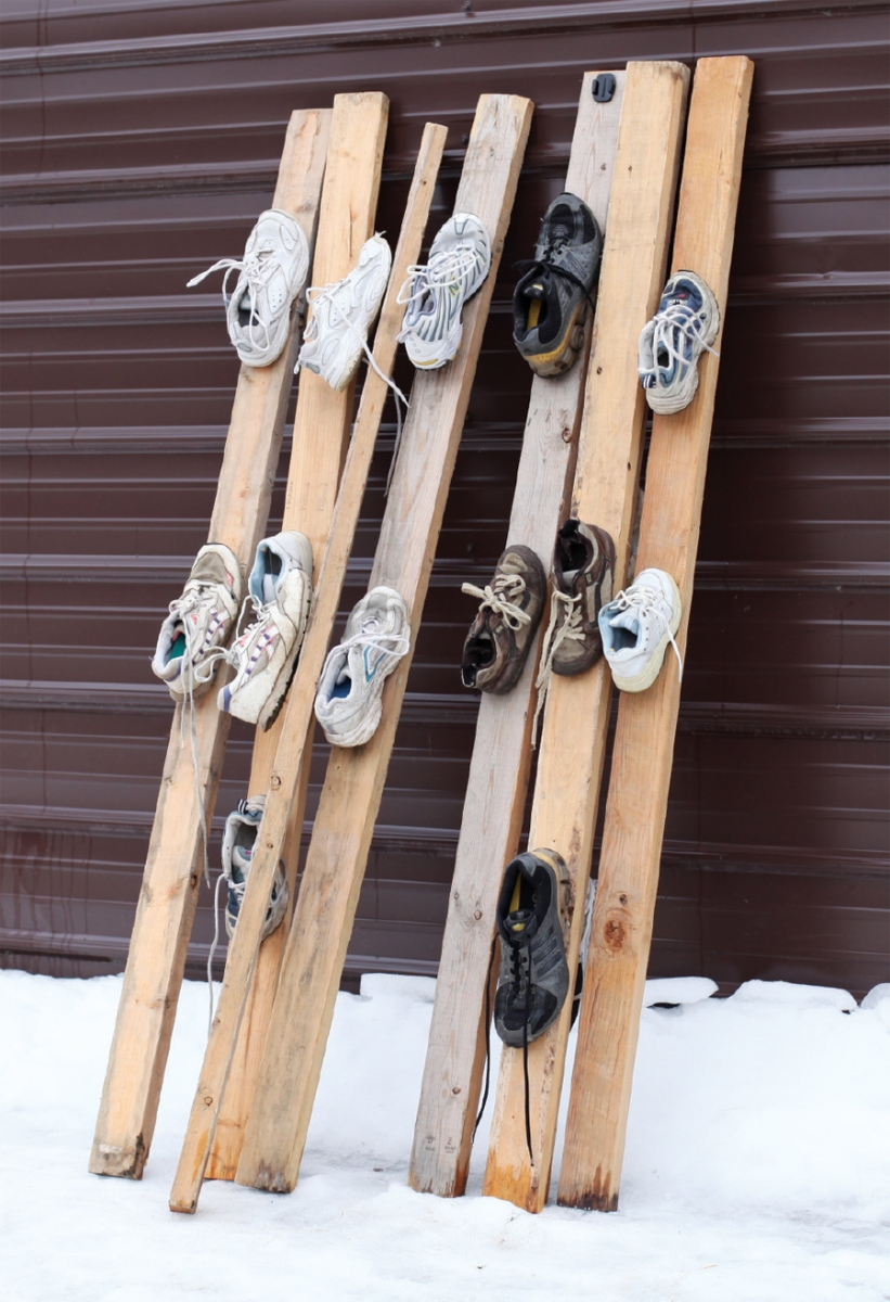 Planks of wood made into skis with tennis shoes attached to them.