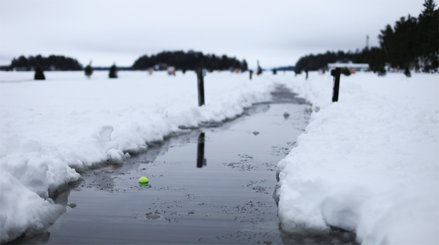 A path of water with a tennis ball in it cuts through a field of snow.
