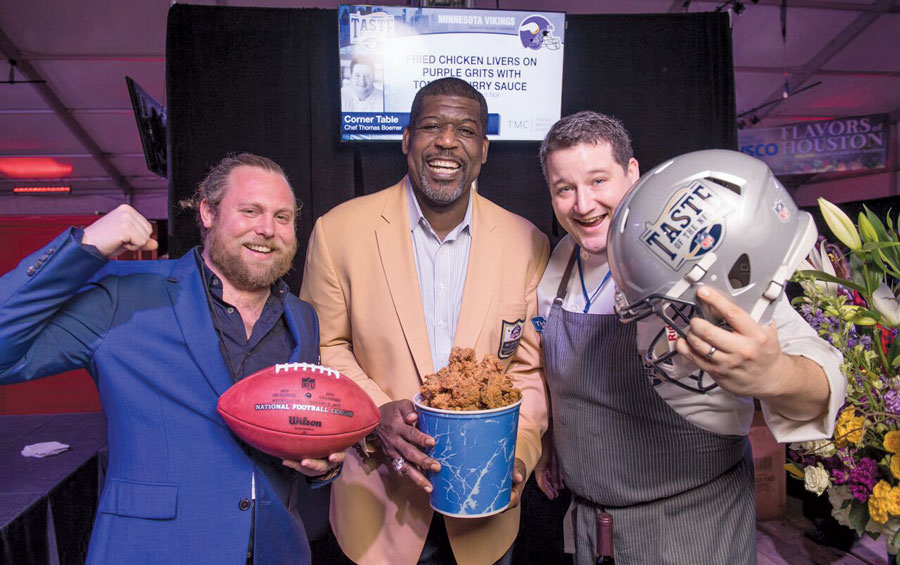 Nick Rancone and Thomas Boemer of Revival stand next to former Viking Randall McDaniel as he holds a bucket of fried chicken.