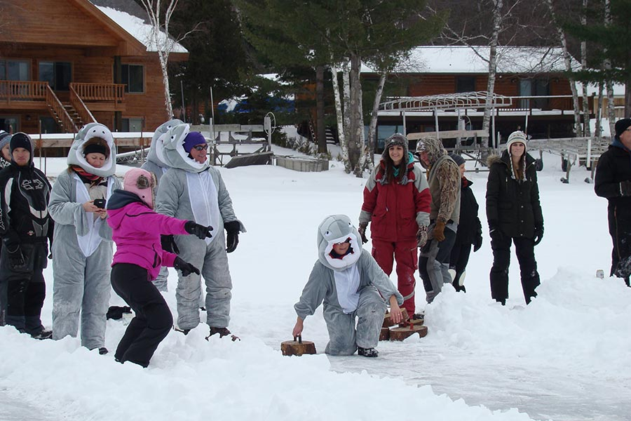 A crowd playing ice bocce ball.