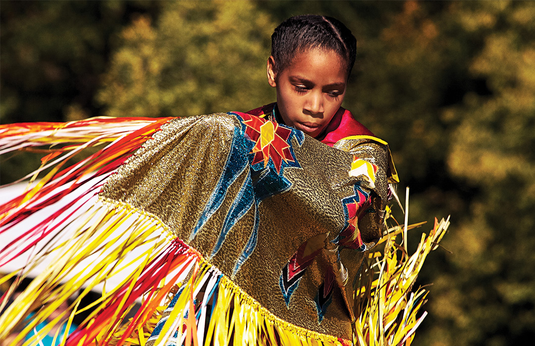 A Native American dancing in traditional garb.