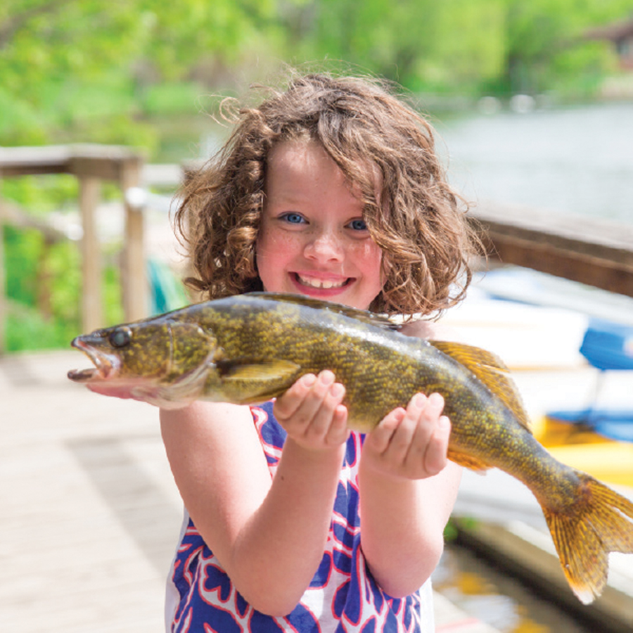 A girl holding a walleye at Ruttger's Bay Lake Lodge.