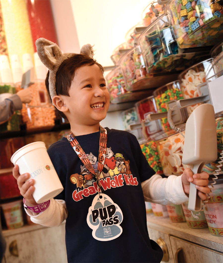A young boy holding a scoop for candy at Great Wolf Lodge in Bloomington, Minnesota.