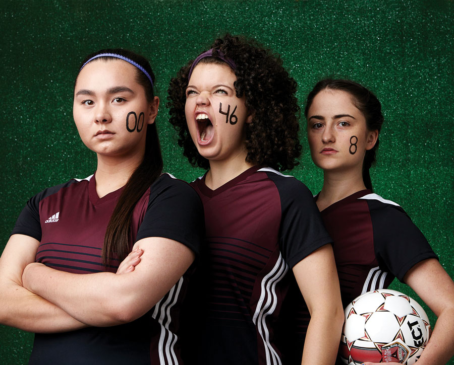 Actresses in soccer uniforms from The Wolves.