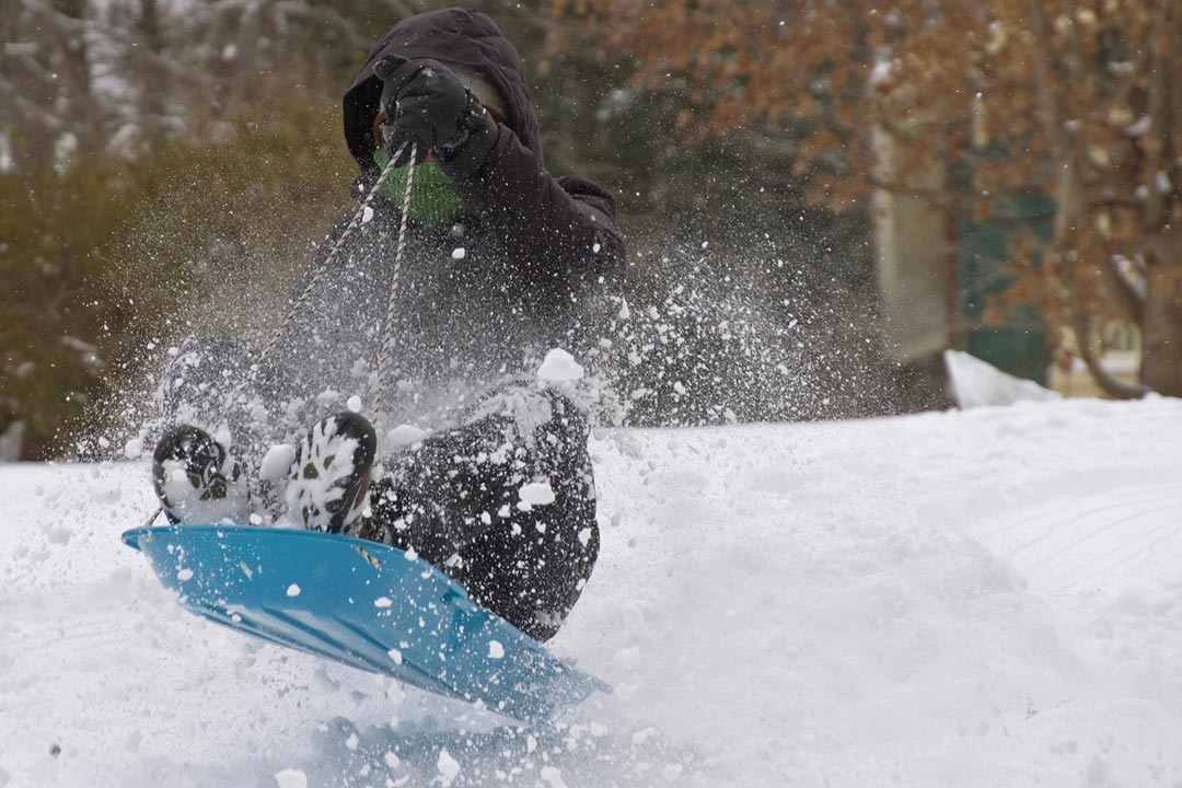 A person sledding down a hill and spraying snow.