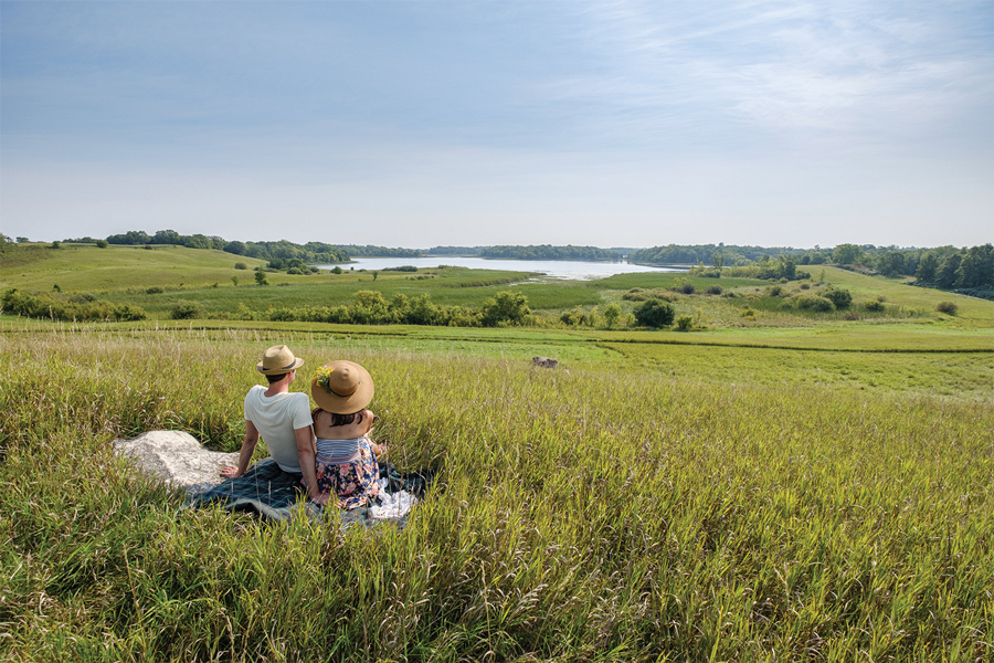 A couple sitting on a grassy hill overlooking some nice scenery in Alexandria, Minnesota.