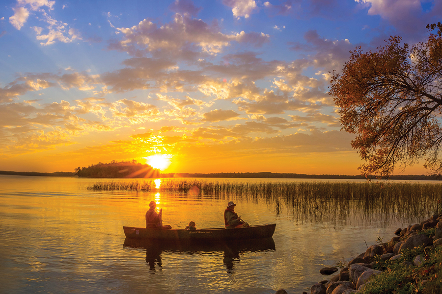 Two people on a fishing boat at sunset in Bemidji, Minnesota.