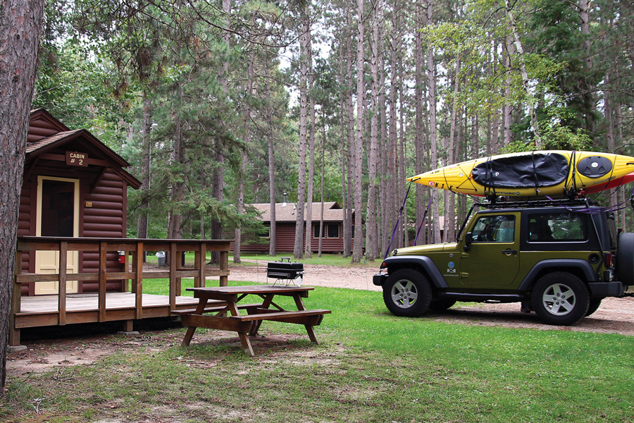 A jeep with a canoe on top parked at a cabin in the forest at Bert's Cabins in Park Rapids, Minnesota.