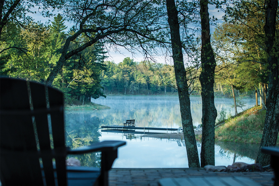 A view of a lake from a patio shows a dock and lush forest surrounding it.