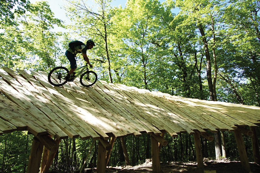 A guy riding a bike on a wooden bridge in the forest at Detroit Mountain Recreation Area in Detroit Lakes, Minnesota.
